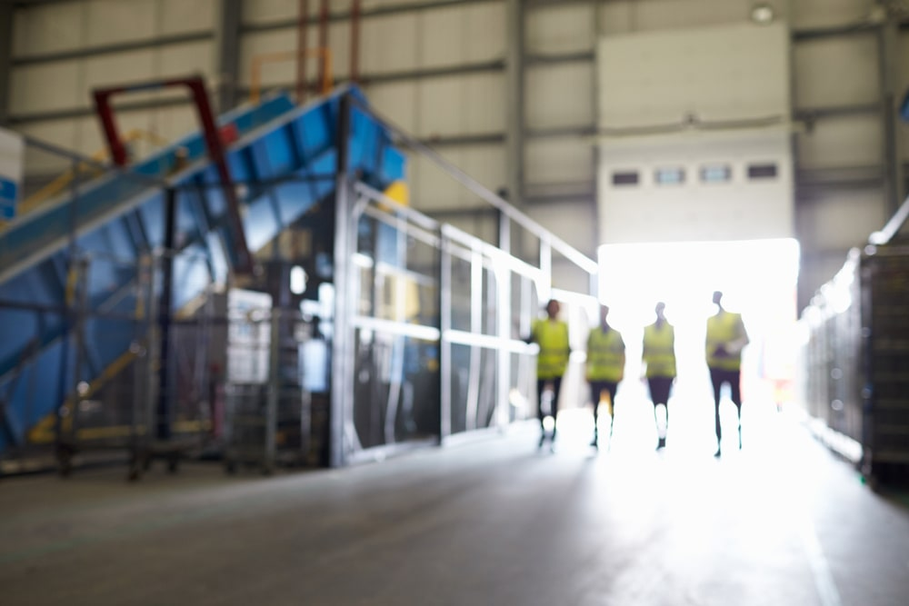 Sécurité et propreté industrielle représenté par une image de 4 caristes marchant en sécurité au sein d'une usine