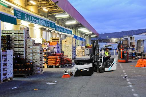 Balayeuse sur chariot en action de nettoyage dans les allés du marché international MERCADI